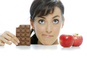 Junge Frau zwischen apfel und schokolade, möchte gerne abnehmen.
