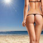 Frau steht am strand nachdem sie an den oberschenkeln abgenommen hat.
